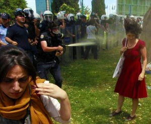"""""""   """"Kırmızılı Kadın"""" (Woman in Red) ünlü sinema adamı Gene Wilder'in hem yönettiği hem de başrolünü oynadığı 1984 tarihli güzel bir komedi filmidir… Kim derdi ki, yaklaşık otuz yıl sonra, 21. yüzyıl Türkiye'sinde, AKP iktidarının ve polis şiddetinin simgesi bir fotoğraf olarak yeniden önümüze gelecek… Osman Orsal çekmiş… Reuters dağıtmış… Taksim Gezi Parkı'nı yok eden ceberut düzenlemeyi ve ağaç kesimini protesto eden halk ile polis arasındaki olaylar sırasında çekilmiş bir kare… Bir kadın: Belli ki protesto için gelmiş oraya… Bir an, """"çılgın kalabalıktan uzak"""" kalmış… Tek başına, polisle karşı karşıya… Ne saldırıyor… Ne kaçıyor… Gözleri yerde... Yüzünde bir acı ifade… Omzundaki çantasını sapından tutmuş… Saçları, sıkılan biber gazının etkisiyle dalgalanmış! Ayakları yere sağlam basıyor… Kaderine boyun eğmiş... Ama direnen… Bir masumiyet heykeli sanki! Karşısında bir polis: Yüzünde gaz maskesi… Dizlerini bükmüş… Boynunu kısmış… Elleri ilerde… Hamle eder pozisyonda… Kırmızılı kadının suratına biber gazı sıkıyor!   """"        * Emre Kongar"""